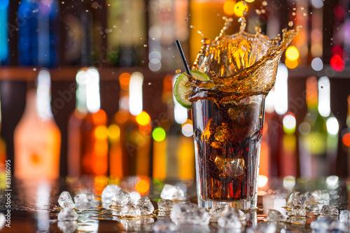 Fototapeta Sklenkou cola na barovým pultem