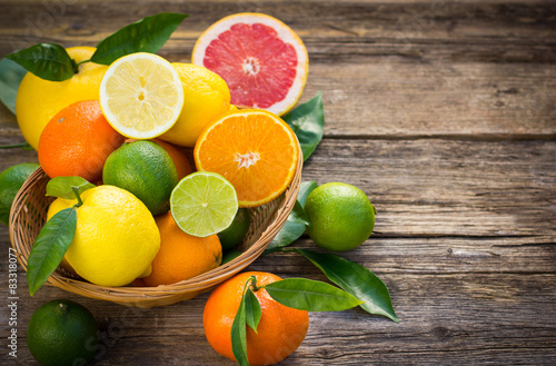 Foto Fresh and juicy citrus fruits in the basket on the rustic table