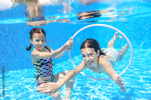 Canvas Print Happy children swim in pool underwater, girls swimming