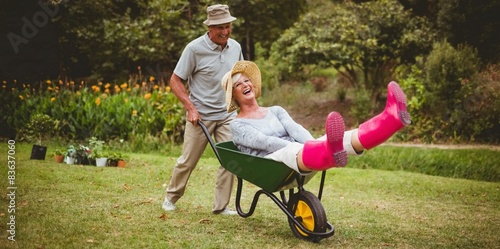 Tableau sur Toile Happy senior couple playing with a wheelbarrow