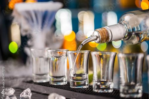 Fotografia Barman pouring hard spirit into glasses