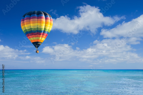 Canvas-taulu Colorful hot air balloon fly over the blue sea