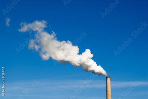 Leinwand Poster Smokestack and horizontal white smoke on blue sky.