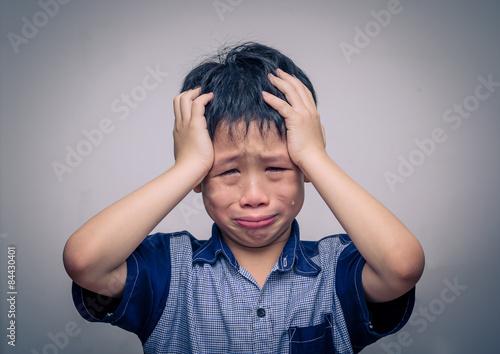 Tableau sur Toile Garçon asiatique pleurer sur fond sombre