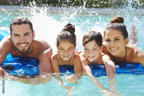 Obraz na plátně Portrét rodiny na nafukovací matrace v bazénu