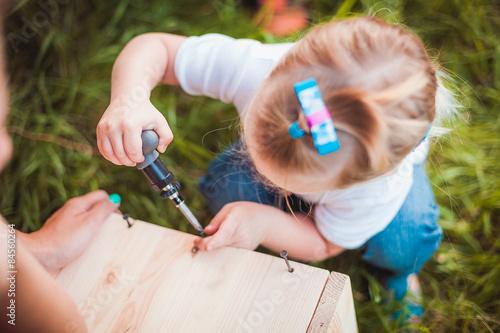 Fotografia Little girl making Wooden birdhouse