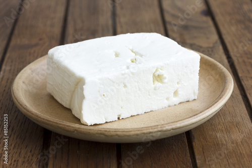Greek feta cheese block on rustic plate and table.