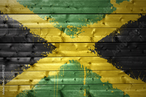 Wallpaper Mural painted jamaican flag on a wooden texture
