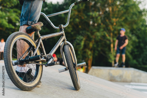 BMX rider on a bike is ready to perform a trick on a ramp in the summer skatepark. soft focus and beautiful bokeh
