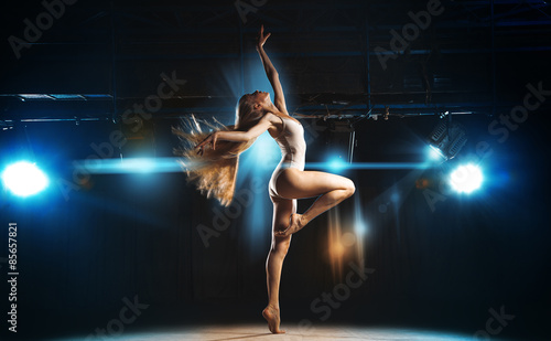 Fotografia Sexy ballerina on stage posing against the backdrop of the spotl