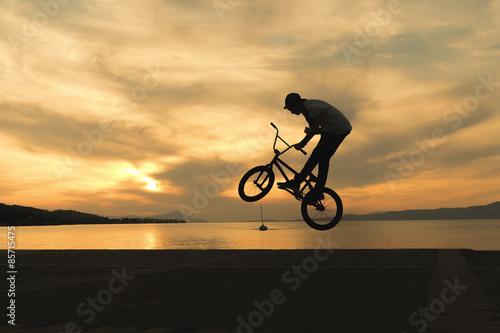 Stunning tricks of bmx biker against the sunset.