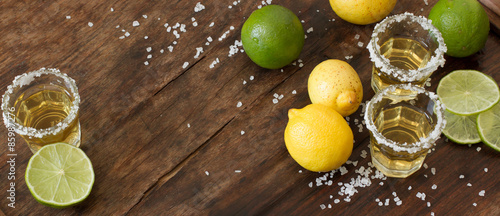 Fotografia tequila lime and lemon on a wooden table