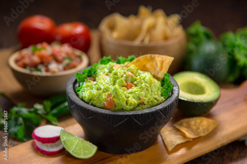 Premium handmade Guacamole from fresh organic avocados with chips on a table with pico de gallo salsa