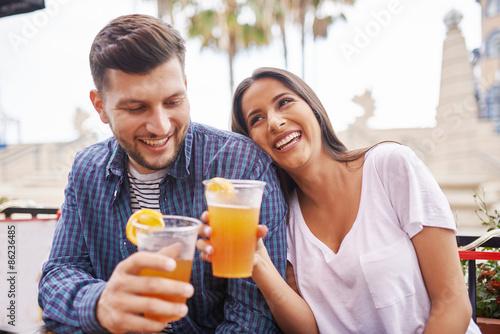 Fotografia romantic hispanic couple drinking beer in outdoor pub