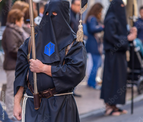 Fotografia, Obraz Nazareno in black carrying a flag during Holy Week in Valladolid.