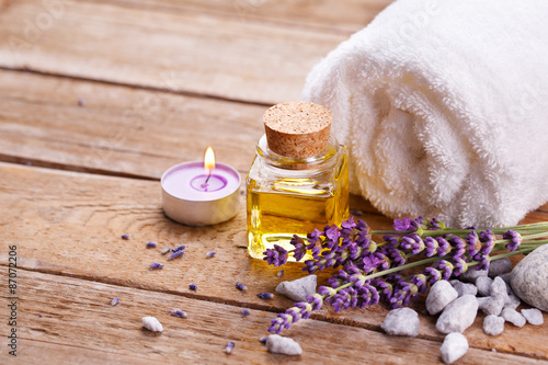 Spa still life with lavender oil, white towel and perfumed candle on natural ...