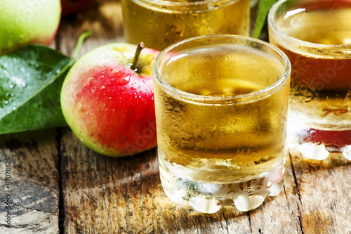Cold apple juice and fresh apples on an old wooden table, select Fototapete