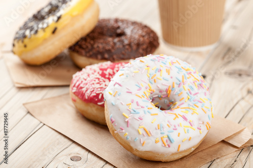 Canvastavla Colorful donuts and paper cup on wooden table