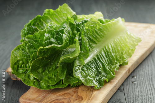Stampa su Tela fresh romain green salad leaves on olive board
