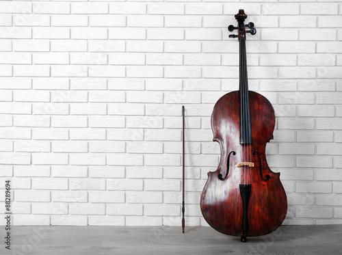 Cello on bricks wall background Fototapeta