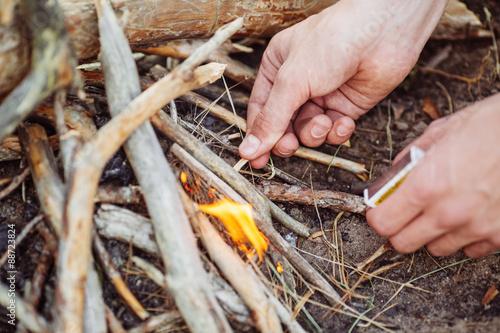 Obraz na płótnie man kindles a fire in summer wood