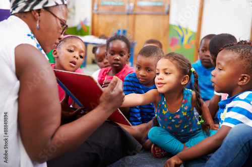 Valokuvatapetti Teacher reading a book with a class of preschool children