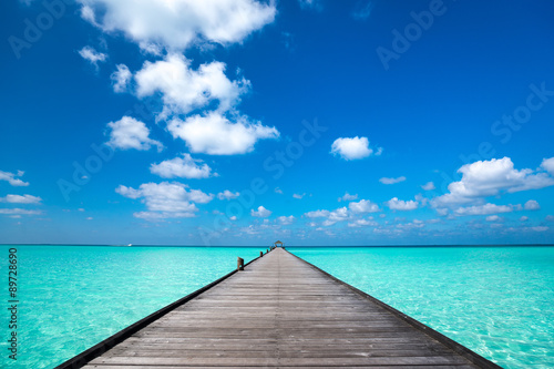 Stampa su Tela Wooden pier with blue sea and sky background
