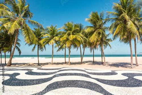 Palm trees and the iconic Copacabana beach mosaic sidewalk, in Rio de Janeiro, Brazil.