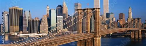This is a close up of the Brooklyn Bridge over the East River. The Manhattan skyline is behind it at sunrise. #90030034