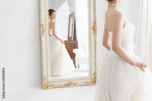 Bride wearing a wedding dress looking at the mirror Fototapet
