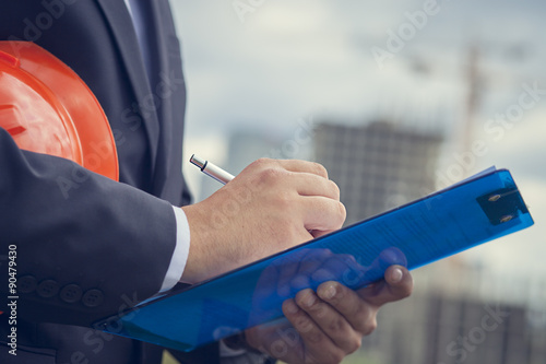 Canvas Print Close-up Worker inspector  holding clipboard on the background of construction