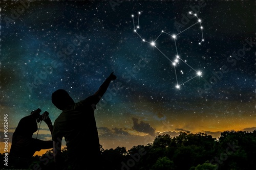 Orion constellation on night sky. Astrology concept. Silhouettes of adult man and child observing night sky.