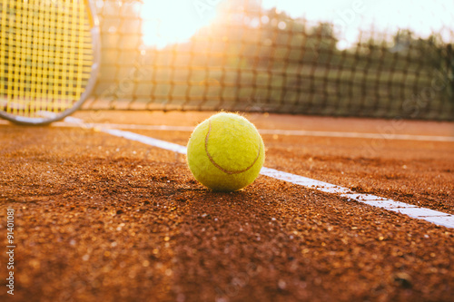 Canvas Print Tennis racket and ball on a clay court