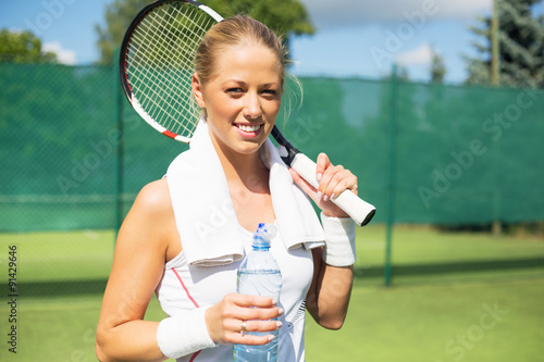 Canvas Print Tennis player holding bottle of water after the practice