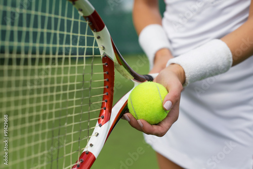 Canvas Print Tennis player holding racket and ball in hands
