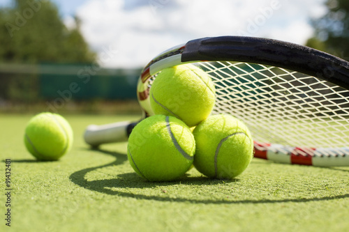 Canvas Print Tennis balls and racket on the grass court
