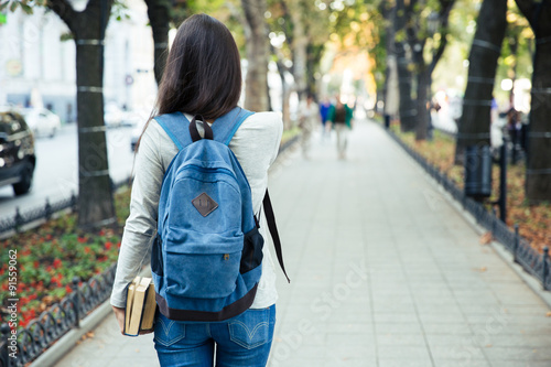Photo Back view portrait of a female student walking