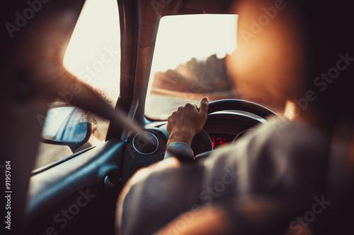 Mężczyzna jazdy samochodem, ręka na kierownicy, patrząc na drodze naprzód, zachód słońca Fototapeta