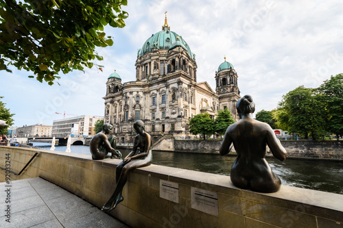 3 statues sit at the riverside. In the background is the Berliner Dom.