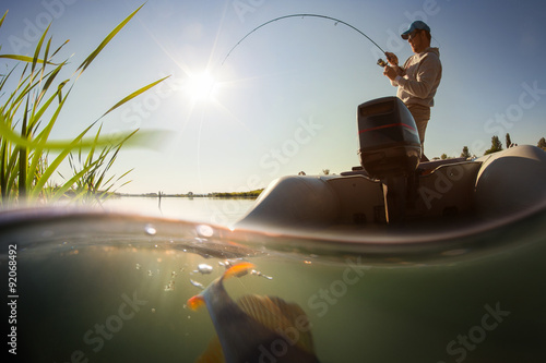 Fotografia, Obraz Fisherman with rod in the boat and underwater view
