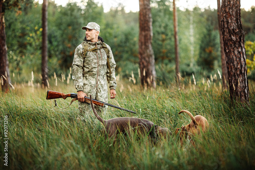 Fotografia yang Hunter with Rifle and Dog in forest