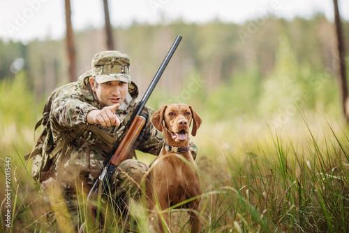 Obraz na plátne hunter with a dog on the forest