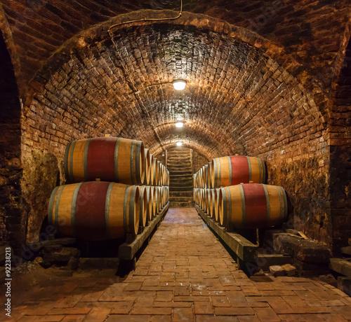 Canvas Print Oak barrels in a underground wine cellar