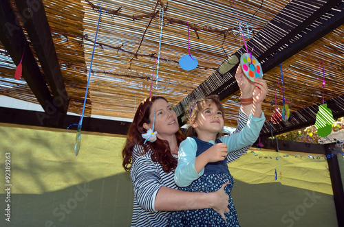 Canvas Print Jewish woman and child decorating their family Sukkah