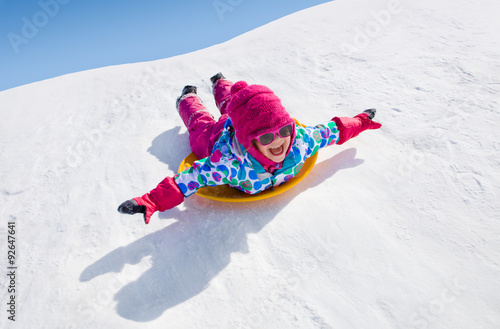 little girl riding on snow slides in winter time