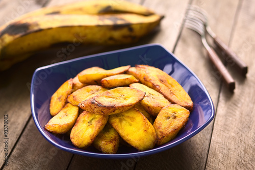 Fried slices of the ripe plantain, which is eaten as snack or accompaniment in South America (Selective Focus, Focus on the front of the upper plantain slice)