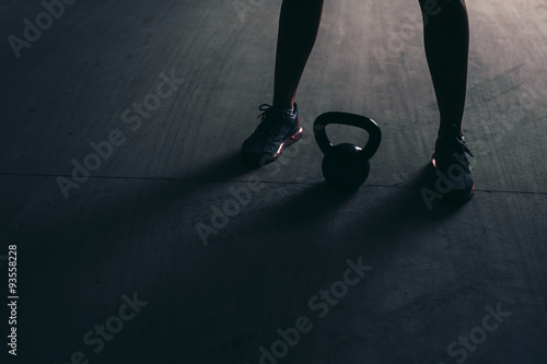 Close-up of legs and a kettlebell lying on a concrete floor