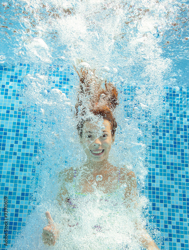 Canvas Print Girl jumps and swims in pool underwater, happy active child has fun in water