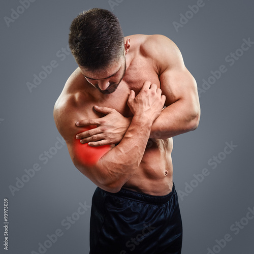 Tablou Canvas Muscular shirtless man with biceps pain over gray background