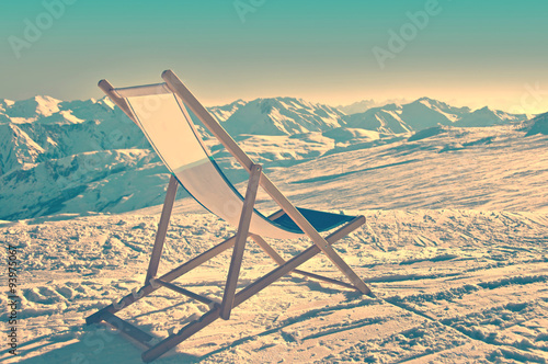 Canvas Print Empty deckchair on the side of a ski slope, vintage process